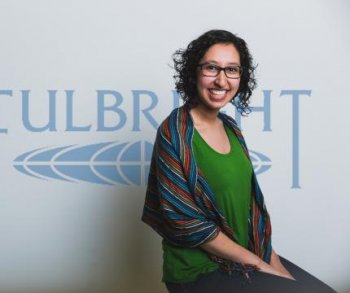 Maria José Palacios Figueroa posing in front of a Fulbright banner in kelly greenshirt and striped shawl