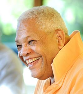 Merle Prim smiling in a very bright orange shirt
