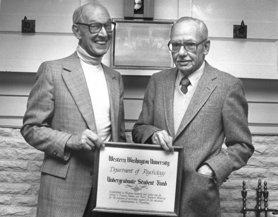 Black and white photo of Adams and Woodring holding an award.