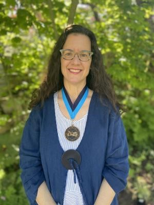 Kimberly Peters wears her award around her neck, pictured outside.
