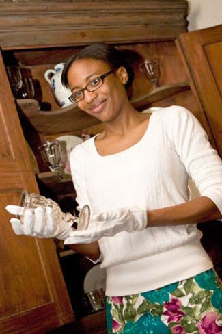 A museology student handles a stemmed glass wearing white gloves