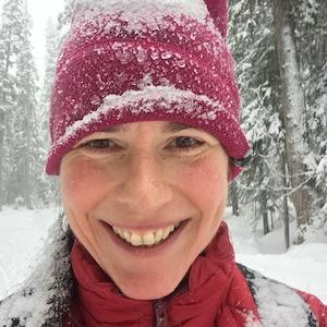 Holly Folk standing in a snowy forest with a red hat and jacket smiling