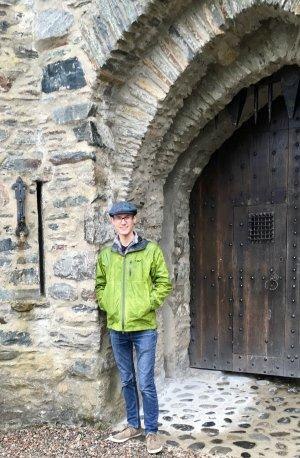 Neal Digre standing next to a castle door in a bright green rain jacket and gray newsboy cap