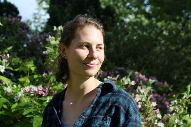 Emily Hillman with curly hair pulled back wearing a dark green plaid shirt, standing in a garden