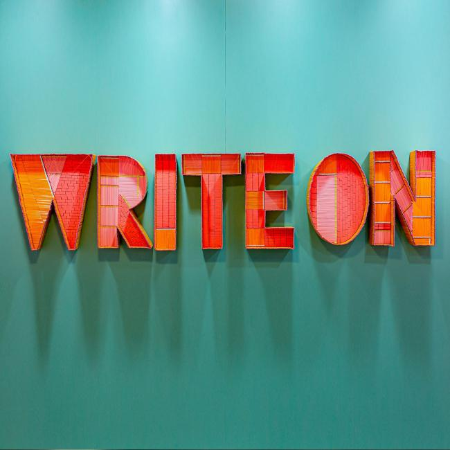 """WRITE ON"" in orange block letters against a teal colored background."