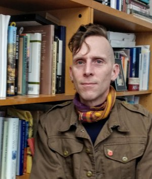 A man stands in front of a shelf of library books